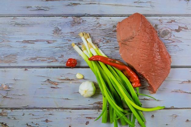Viande de steak de bœuf cru aux herbes et épices sur une planche à découper en bois Photo Premium