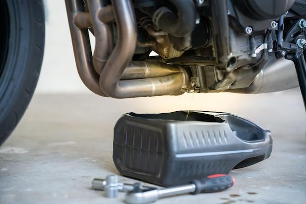 Vidanger l'huile usée du moteur par le bouchon de vidange. changer l'huile dans un moteur de moto Photo Premium
