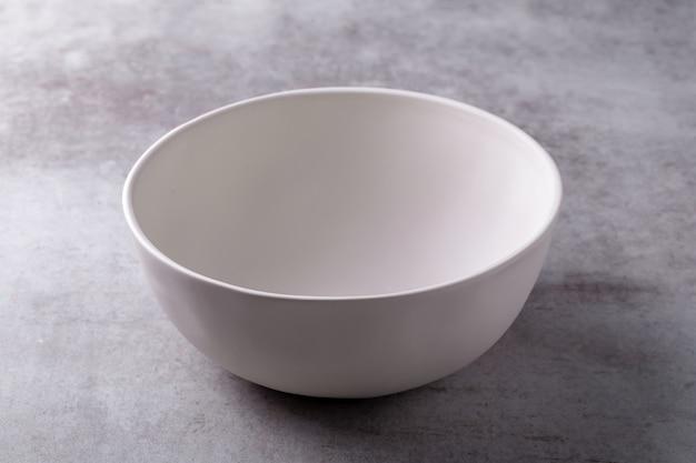 Vide bol blanc en céramique blanche sur panneau de ciment Photo Premium