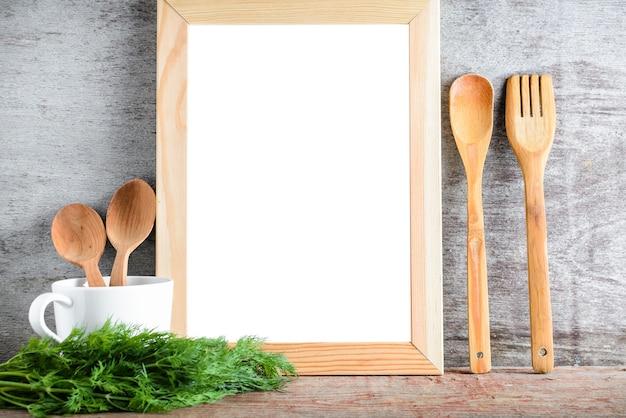Vide cadre blanc isolé et accessoires de cuisine sur une table en bois. Photo Premium