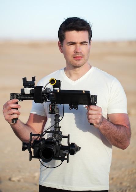 Vidéaste avec équipement steadicam sur la plage Photo Premium