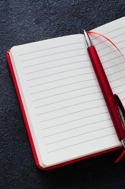 Vider le cahier rouge ouvert avec un stylo rouge sur fond sombre Photo Premium