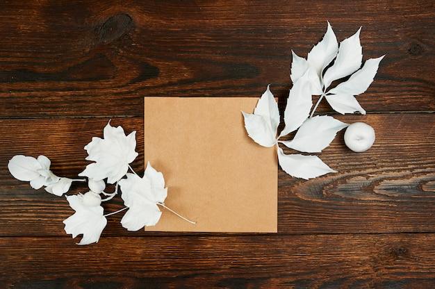Vider la feuille de papier kraft vide à plat sur la maquette pour votre espace de copie de composition de lettres, art ou composition manuscrite, vue de dessus. composition d'automne faite de feuilles blanches sur un fond en bois brun foncé Photo Premium