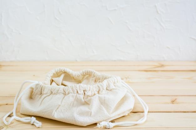Vider le sac de toile ouverte sur les liens pour la nourriture sur une table en bois naturel. concept zéro déchet Photo Premium