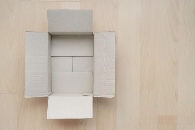 Videz la boîte en carton rectangulaire ouverte sur le bois. Photo Premium