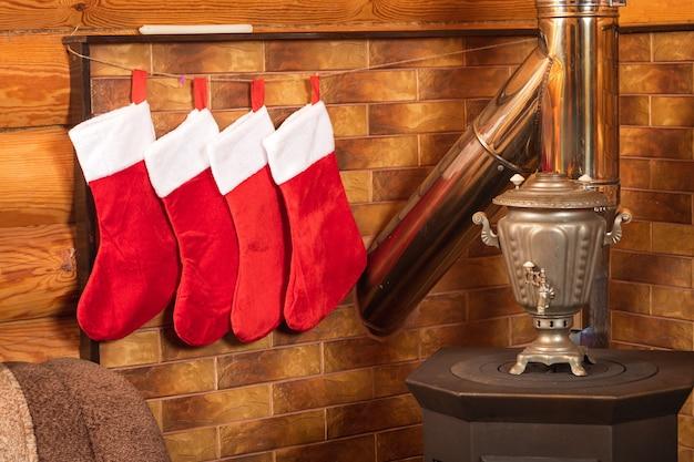 La Vie Encore Du Nouvel An De Quatre Chaussettes Rouges Du Nouvel An Pour Les Cadeaux, Une Cheminée Sur Le Fond D'un Mur En Bois Photo Premium