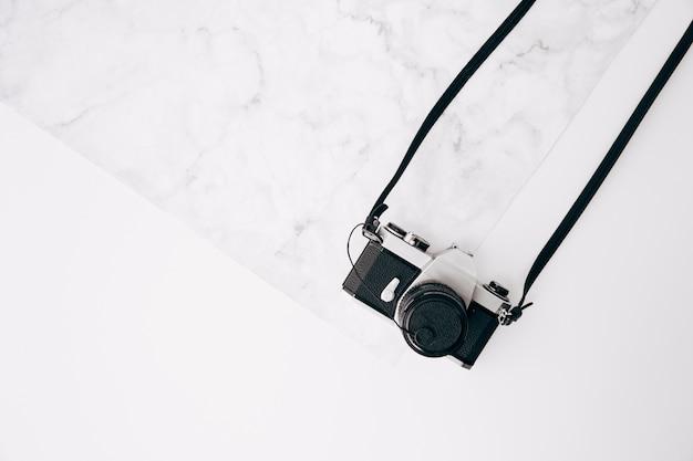 Un vieil appareil photo rétro vintage sur marbre fond texturé et blanc Photo gratuit