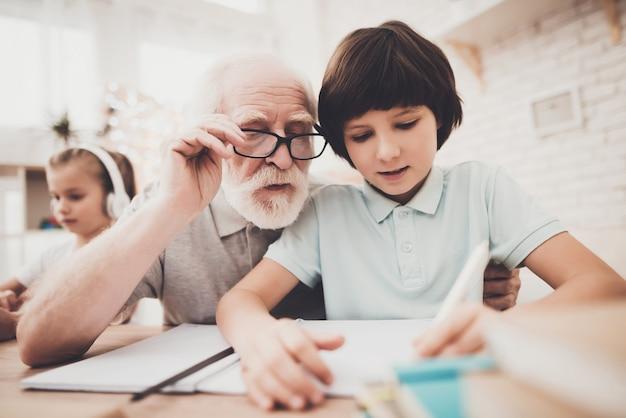 Un Vieil Homme Aide Un Enfant Qui Apprend Dur à Faire Ses Devoirs. Photo Premium