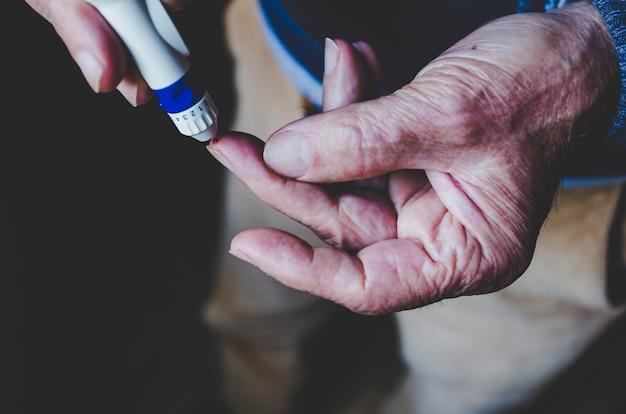 Vieil homme à l'aide d'un stylo lancette sur fond noir Photo Premium