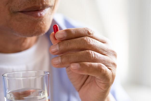 Vieil Homme Asiatique Prenant En Pilule Et Une Autre Main Tenant Un Verre Photo Premium