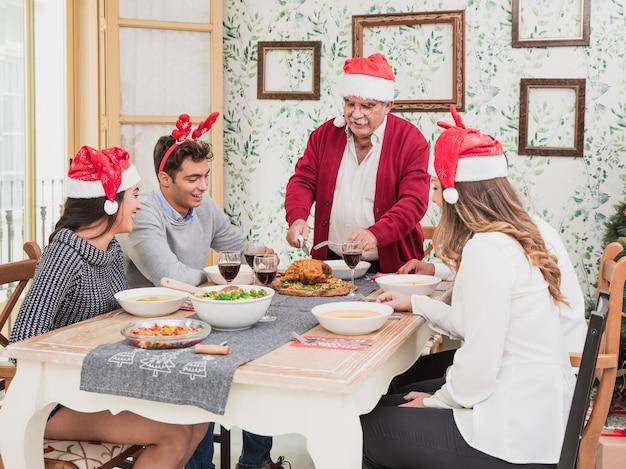 Vieil homme au bonnet de noel coupant le poulet cuit au four sur la table de fête Photo gratuit