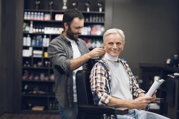 Vieil homme aux cheveux gris se trouve dans la styliste dans le salon de coiffure. Photo Premium