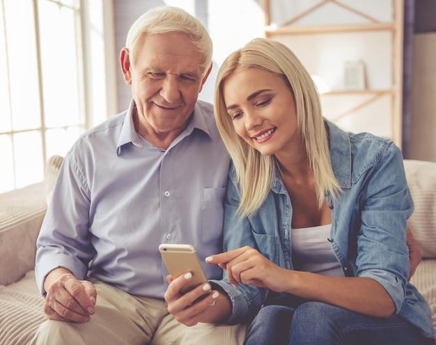 Vieil homme et belle jeune fille utilisent un smartphone. Photo Premium