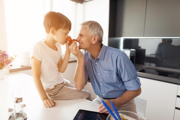 Vieil homme en chemise bleue et son petit-fils qui est assis à côté de lui. Photo Premium