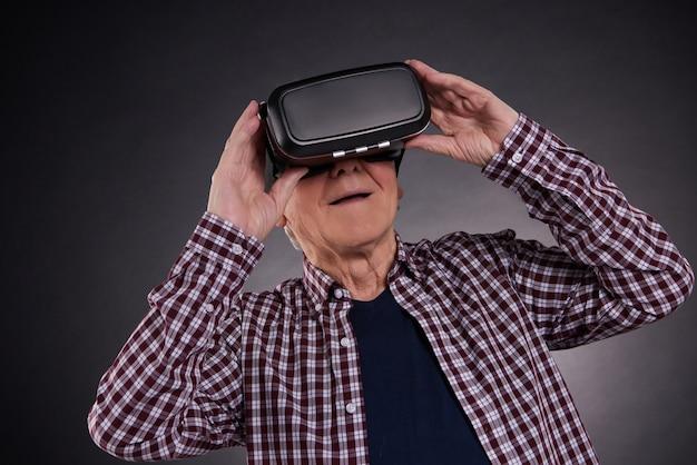 Vieil homme dans des lunettes de réalité virtuelle sur fond noir. Photo Premium