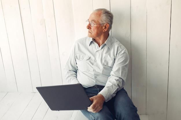 Vieil Homme élégant Assis à La Maison Et à L'aide D'un Ordinateur Portable Photo gratuit