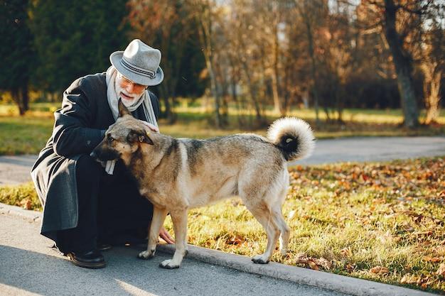 Vieil homme élégant dans un parc d'automne ensoleillé Photo gratuit