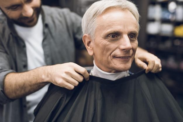Le vieil homme est assis dans la chaise du coiffeur Photo Premium