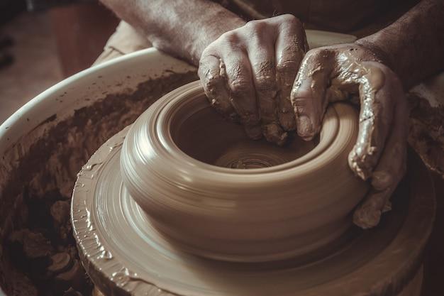 Vieil homme faisant un pot à l'aide d'un potier en studio. fermer. Photo Premium