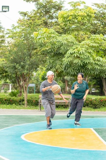 Un vieil homme et une femme vont jouer au basket avec tant de joie au bangyai park nonthaburi Photo Premium