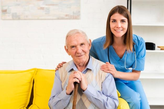 Vieil homme et infirmière assis sur un canapé jaune tout en regardant la caméra Photo gratuit