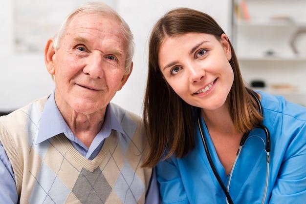 Vieil homme et infirmière en regardant la caméra Photo gratuit