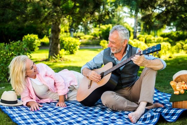Vieil homme jouant de la guitare pour sa femme Photo gratuit