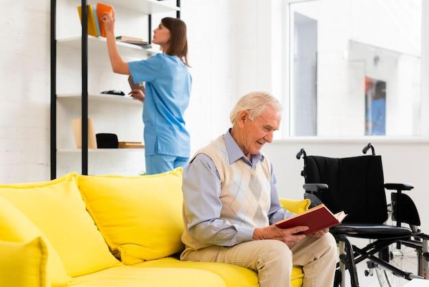 Vieil homme lisant un livre assis sur un canapé jaune Photo gratuit