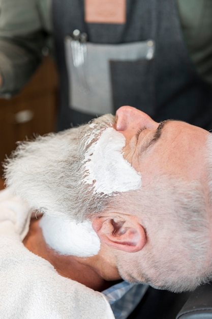 Vieil homme avec une mousse à raser sur le visage et le cou Photo gratuit