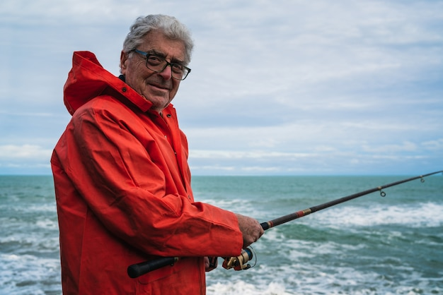 Vieil Homme Pêchant Dans La Mer. Photo Premium
