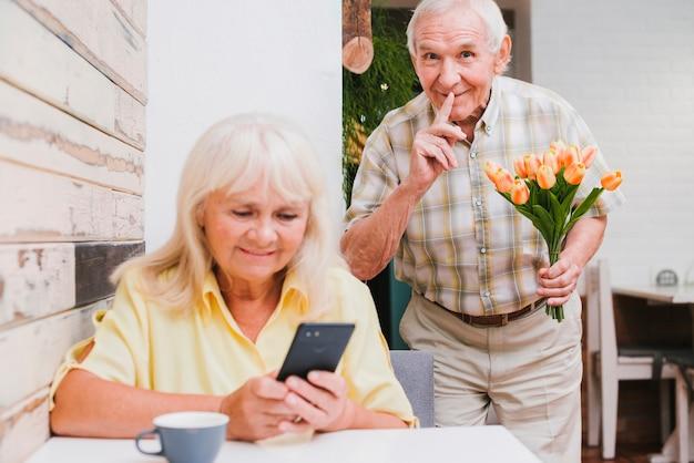 Vieil homme prépare une surprise avec bouquet pour femme Photo gratuit