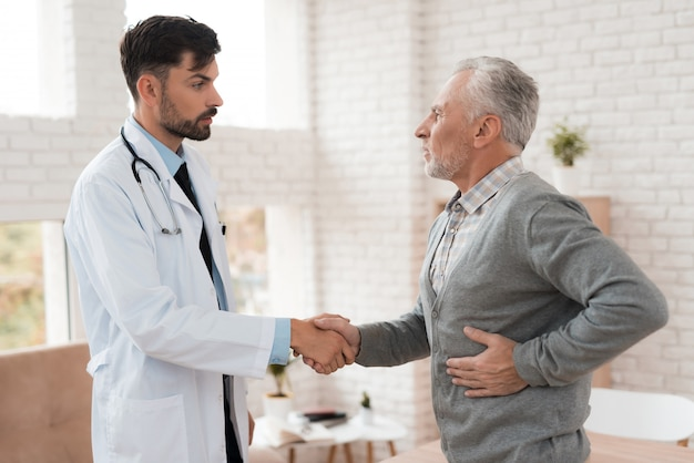 Le vieil homme se plaint au docteur de la douleur dans la rate. Photo Premium
