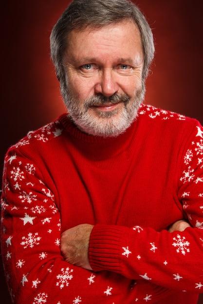 Vieil Homme Souriant Dans Un Pull De Noël Rouge Photo gratuit