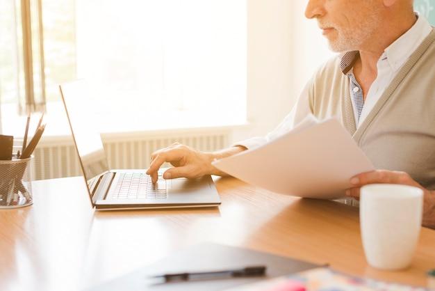 Vieil homme travaillant sur un ordinateur portable Photo gratuit