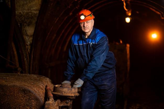 Un vieil homme vêtu d'une combinaison de travail et d'un casque Photo Premium
