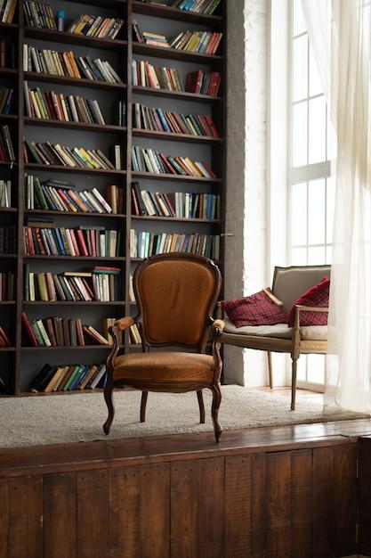 Vieille armoire avec beaucoup de livres et une chaise à côté Photo Premium