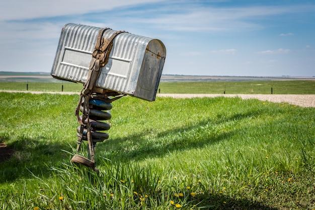 Une vieille boîte aux lettres en métal avec une bride enroulée autour de celle-ci dans une région rurale de la saskatchewan, canada Photo Premium