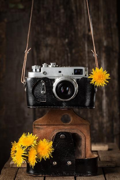 Vieille caméra et pissenlits jaunes, nature morte Photo Premium