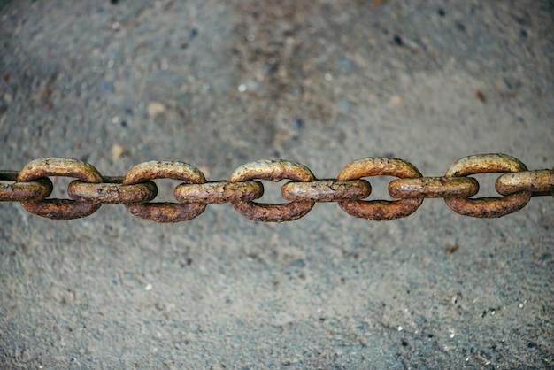 Vieille chaîne rouillée oxydée suspendue sur l'asphalte se bouchent avec l'espace de la copie Photo Premium