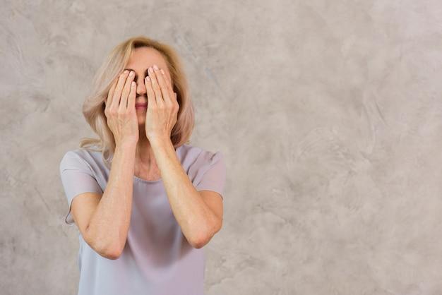 Vieille dame couvrant son visage avec espace copie Photo gratuit