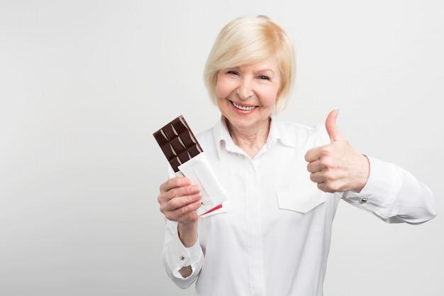 La Vieille Dame Tient Une Barre De Bon Chocolat Et Regarde Droit Devant. Elle En Aimait Le Goût. Elle Pourrait Recommander Ce Chocolat Comme Le Meilleur. Photo Premium