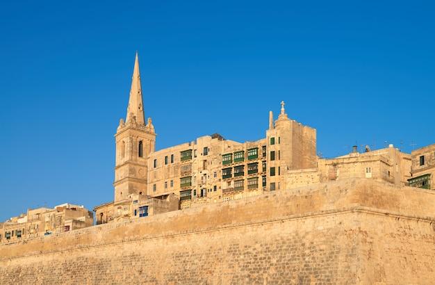Une vieille église de grès et des maisons à la valette, malte Photo Premium