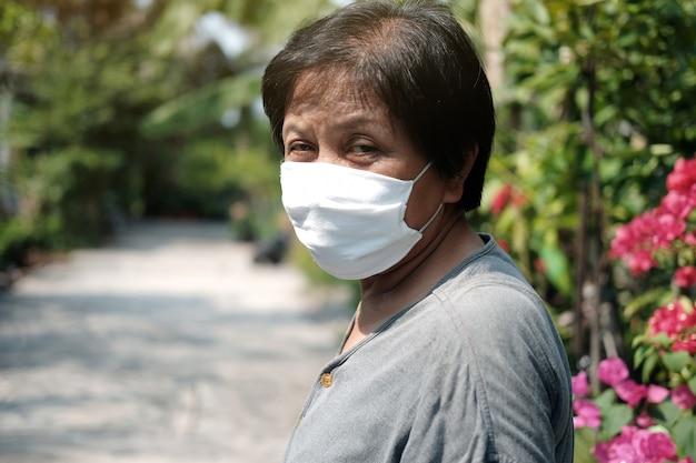 Vieille Femme Asiatique Portant Un Masque En Tissu Blanc Pour Prévenir Le Virus Covid-19 Ou Corona En Thaïlande Et La Protection Contre La Pollution Atmosphérique Pm 2,5 Photo Premium