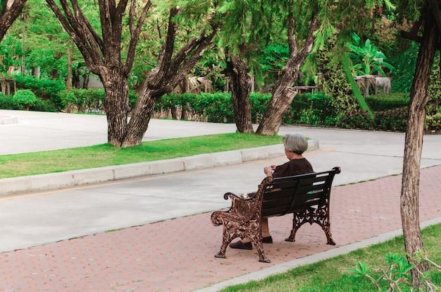 Vieille femme assise sur un banc au parc Photo Premium