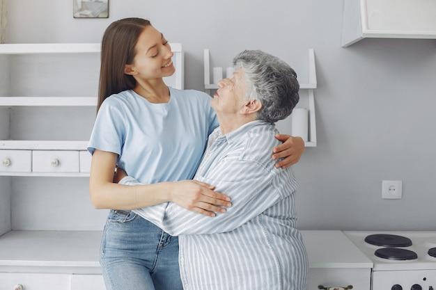 Vieille femme dans une cuisine avec jeune petite-fille Photo gratuit