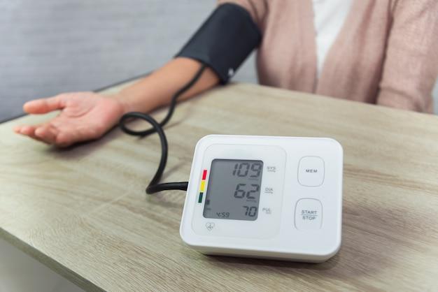 Vieille femme avec manomètre vérifiant le niveau de pression artérielle sur la table Photo Premium
