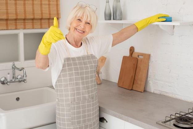 Vieille Femme Nettoyant La Cuisine Avec Des Gants Photo gratuit