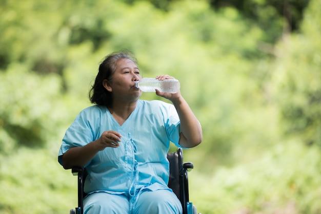 Vieille femme s'asseoir sur fauteuil roulant avec une bouteille d'eau après avoir pris un médicament Photo gratuit