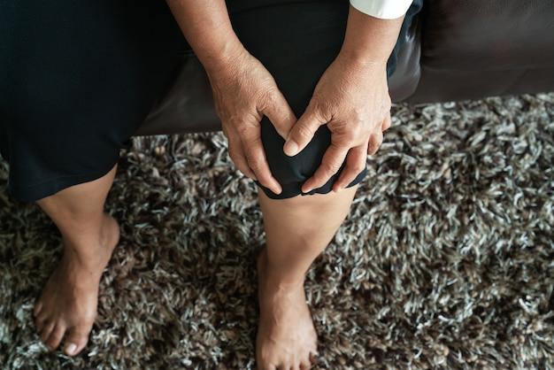 Vieille femme souffrant d'une douleur au genou à la maison, concept de problème de santé Photo Premium