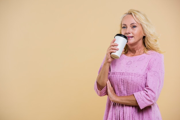 Vieille femme avec une tasse de café en regardant la caméra Photo gratuit